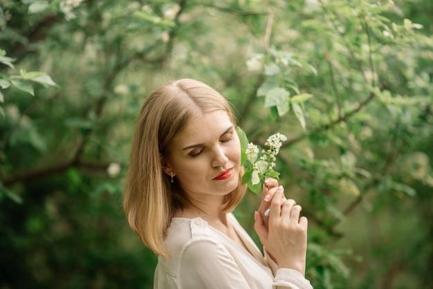 Giovane donna in posa nella foresta di primavera
