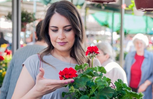 Giovane donna in possesso di geranio in vaso di argilla al centro del giardino. giardinaggio, piantare - donna con fiori di geranio