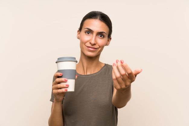 Giovane donna in possesso di un caffè da asporto che invita a venire con la mano, felice che tu sia venuto