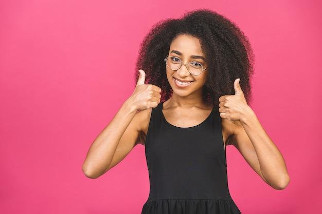 Giovane donna in rosa dando un pollice in alto gesto.