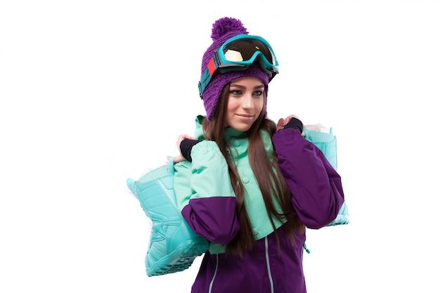 Giovane donna in scarponi da neve viola tenere attrezzatura da sci