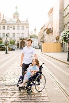Giovane donna in sedia a rotelle che passeggia in città insieme al suo giovane uomo bello