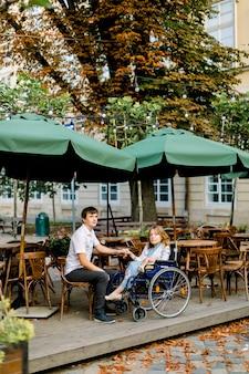 Giovane donna in sedia a rotelle, trascorrere del tempo insieme al ragazzo maschio