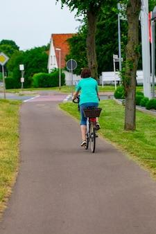Giovane donna in sella a una bicicletta, vista posteriore.