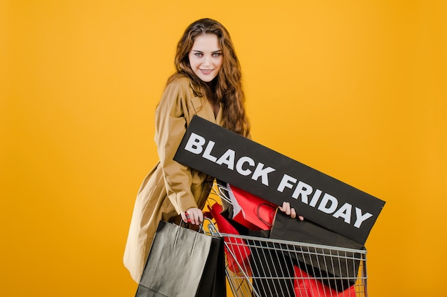Giovane donna in trench autunnale con il segno del venerdì nero e sacchetti colorati nel carrello isolato su giallo