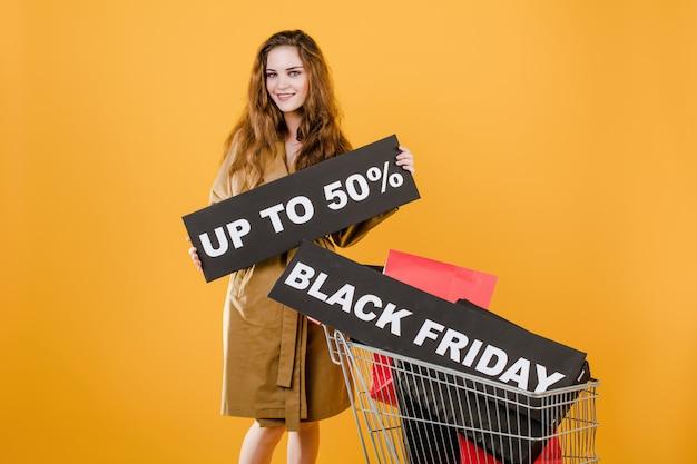 Giovane donna in trench con venerdì nero segno del 50% e colorate shopping bag nel carrello isolato su giallo