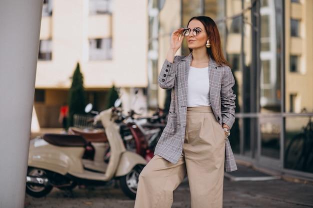Giovane donna in tuta in piedi dallo scooter