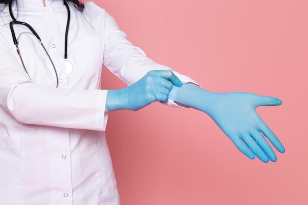 Giovane donna in tuta medica bianco guanti blu maschera protettiva blu con stetoscopio sul rosa
