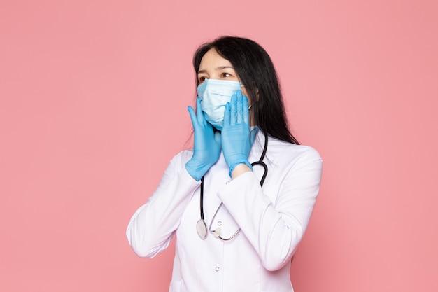 Giovane donna in tuta medica bianco guanti blu maschera protettiva blu sul rosa
