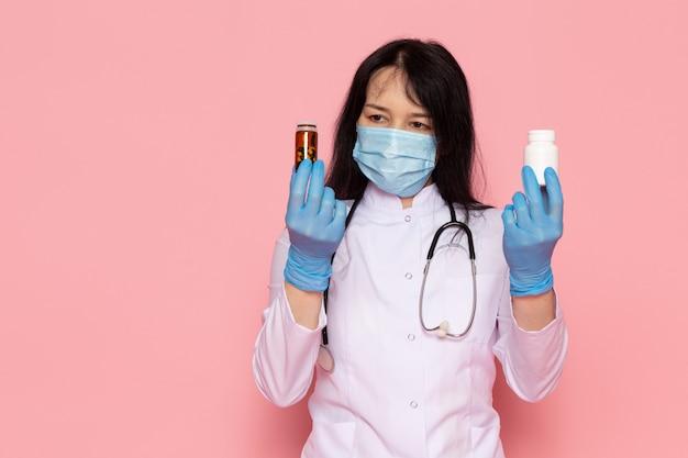 Giovane donna in tuta medica bianco guanti blu maschera protettiva blu tenendo lattine con pillole su rosa