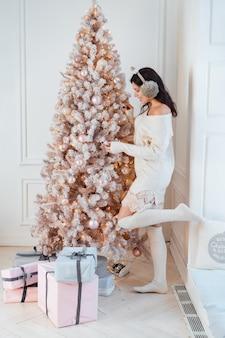 Giovane donna in un abito elegante vicino all'albero di natale