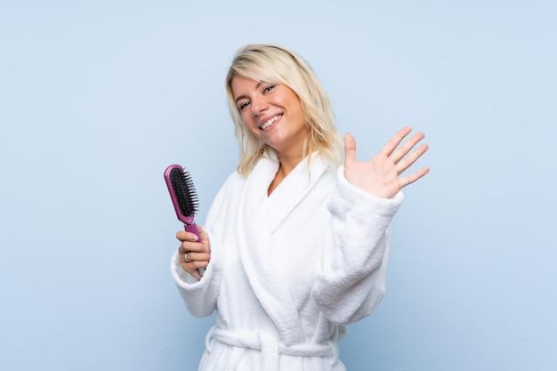 Giovane donna in un accappatoio con il pettine dei capelli che saluta con la mano con l'espressione felice