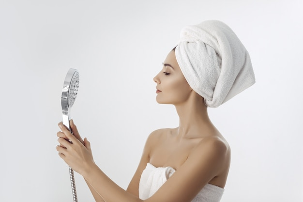 Giovane donna in un asciugamano che tiene la testa della doccia
