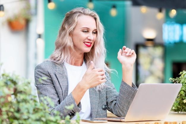 Giovane donna in un caffè di strada con un computer portatile.