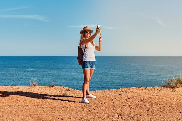 Giovane donna in un cappello che fa un selfie davanti alla costa in estate