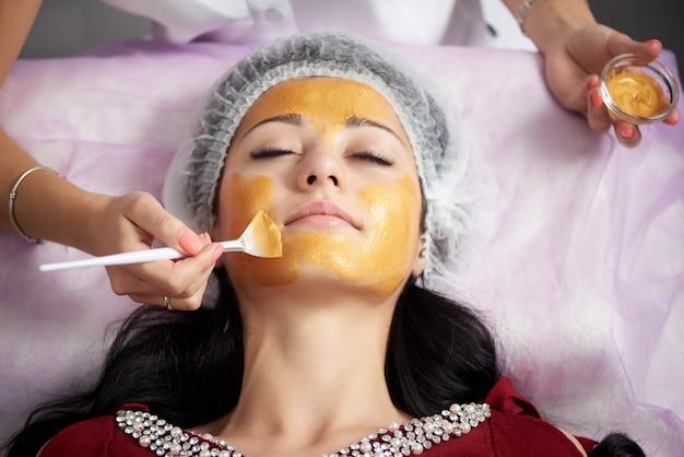 Giovane donna in un cappello speciale sulla sua testa che applica la maschera facciale dell'oro.
