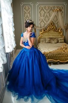 Giovane donna in un lussuoso abito blu e una corona