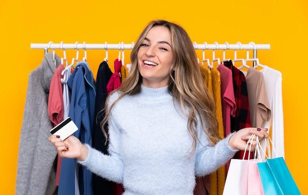 Giovane donna in un negozio di abbigliamento in possesso di una carta di credito e con borse della spesa