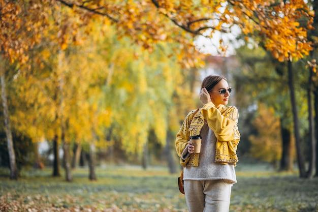 Giovane donna in un parco di autunno che beve caffè