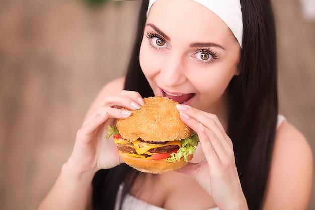 Giovane donna in un raffinato ristorante mangia un hamburger, si comporta in modo improprio