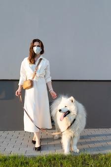 Giovane donna in un vestito bianco che cammina il suo cane