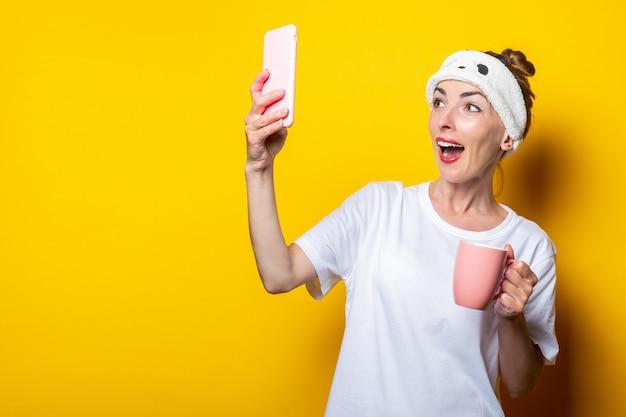Giovane donna in una benda per dormire e con una tazza di caffè fa un selfie, in posa su uno sfondo giallo.