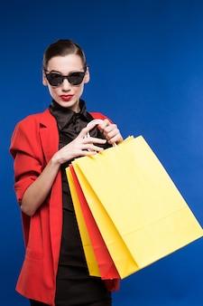 Giovane donna in una giacca e con le borse