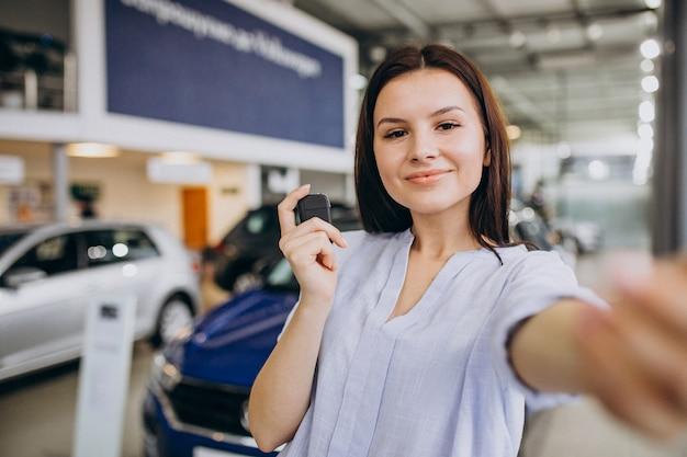 Giovane donna in una sala d'esposizione dell'automobile che sceglie un'automobile