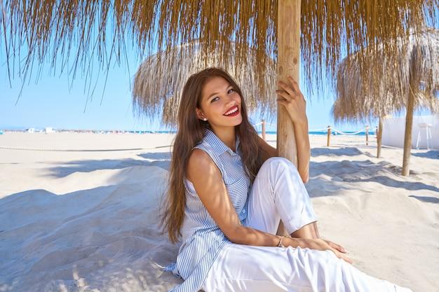 Giovane donna in una spiaggia sotto l'ombrellone