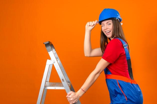 Giovane donna in uniforme della costruzione e casco di sicurezza blu sulla scala che sbatte le palpebre esaminando la macchina fotografica su fondo arancio isolato