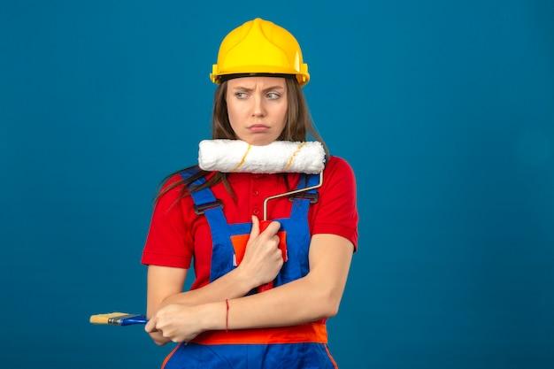 Giovane donna in uniforme di costruzione e casco di sicurezza giallo che pensano il rullo di pittura pensieroso della tenuta di espressione che sta sul fondo blu