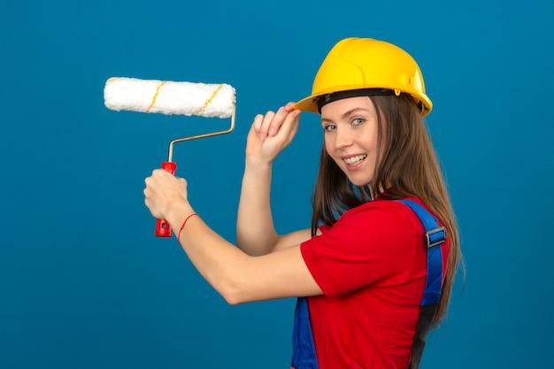 Giovane donna in uniforme di costruzione e casco di sicurezza giallo che sorride e che tiene il rullo di pittura che sta sul fondo blu