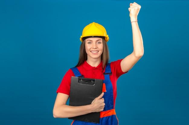 Giovane donna in uniforme di costruzione e casco di sicurezza giallo con la lavagna per appunti che alza pugno con il sorriso sul concetto del vincitore del fronte che sta sul fondo blu
