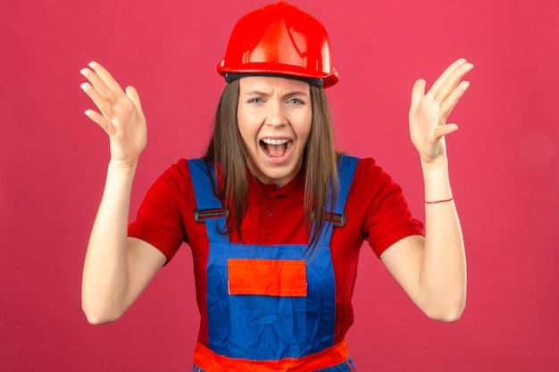 Giovane donna in uniforme di costruzione e casco di sicurezza rosso che grida con l'espressione aggressiva e le braccia alzate in piedi su sfondo rosa scuro
