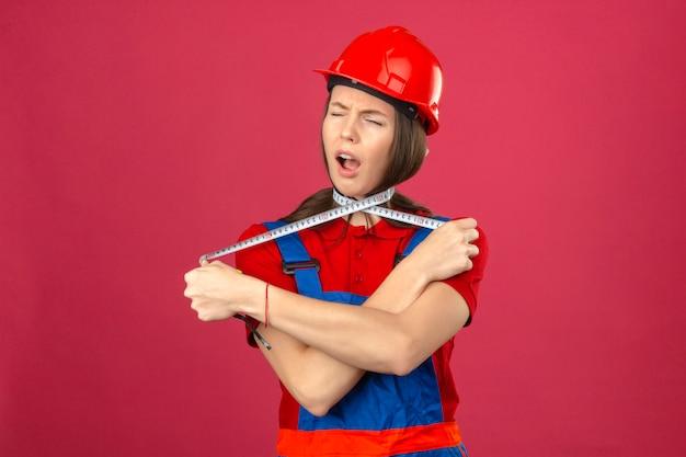 Giovane donna in uniforme di costruzione e casco di sicurezza rosso che grida e che si soffoca con nastro adesivo di misurazione su fondo rosa scuro