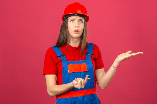 Giovane donna in uniforme di costruzione e casco di sicurezza rosso che sembrano modo laterale contando e pensando stando sul fondo rosa scuro