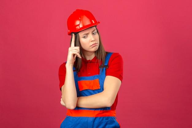 Giovane donna in uniforme di costruzione e casco di sicurezza rosso guardando lateralmente con espressione dubbiosa e scettica su sfondo rosa scuro