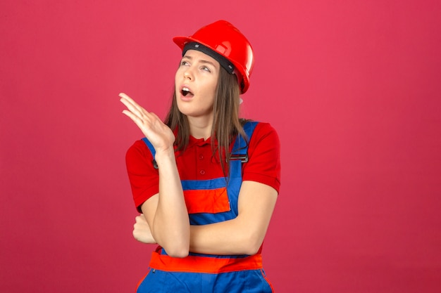 Giovane donna in uniforme di costruzione e casco di sicurezza rosso guardando lateralmente pensando a un'idea su sfondo rosa scuro