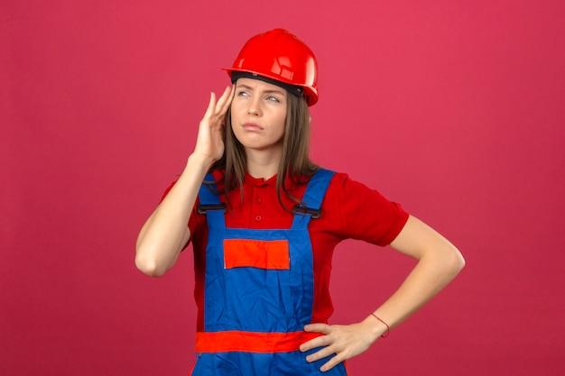 Giovane donna in uniforme di costruzione e casco di sicurezza rosso guardando lateralmente toccando la testa con un mal di testa in piedi su sfondo rosa scuro