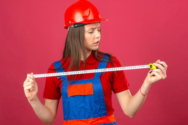 Giovane donna in uniforme di costruzione e casco di sicurezza rosso seriamente guardando il nastro di misurazione su sfondo rosa scuro