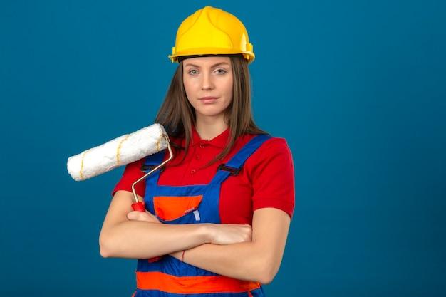 Giovane donna in uniforme di costruzione e rullo di vernice giallo della tenuta del casco di sicurezza che sta con le armi attraversate su fondo blu