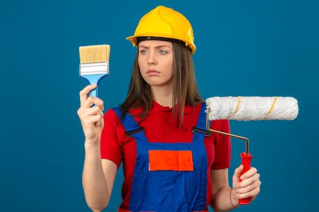 Giovane donna in uniforme di costruzione e rullo giallo della spazzola e della tenuta della tenuta del casco di sicurezza e guardarlo con il fronte serio che sta sul fondo blu