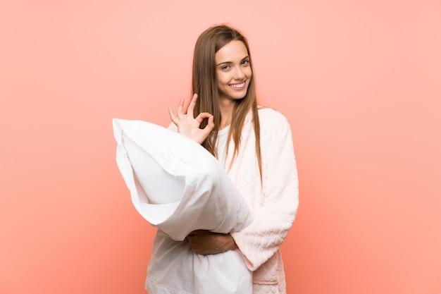 Giovane donna in vestaglia sopra la parete rosa che mostra un segno giusto con le dita