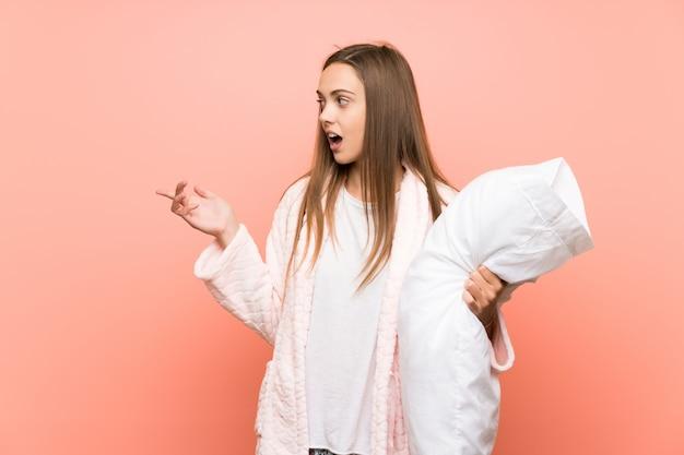 Giovane donna in vestaglia sopra la parete rosa sorpreso e puntando il dito verso il lato