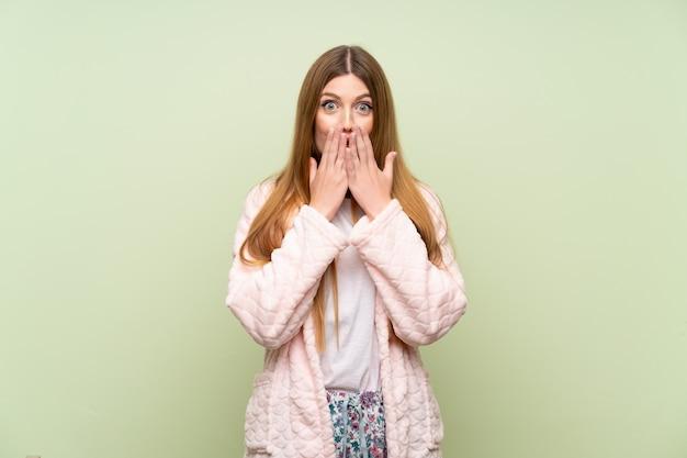 Giovane donna in vestaglia sopra la parete verde con espressione facciale sorpresa