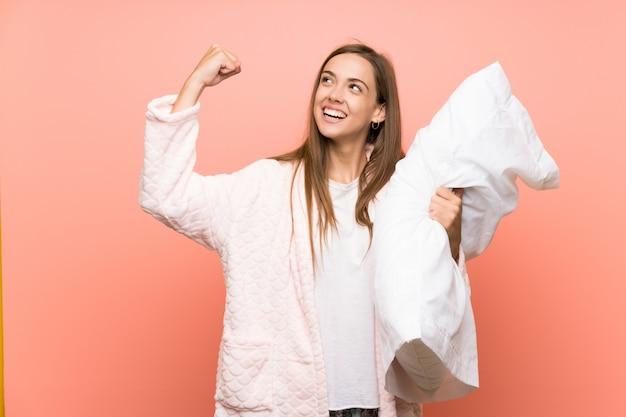 Giovane donna in vestaglia sul muro rosa che celebra una vittoria