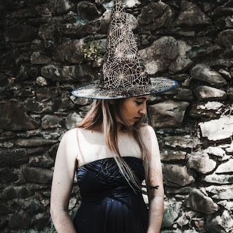 Giovane donna in vestito e cappello della strega che osserva da parte