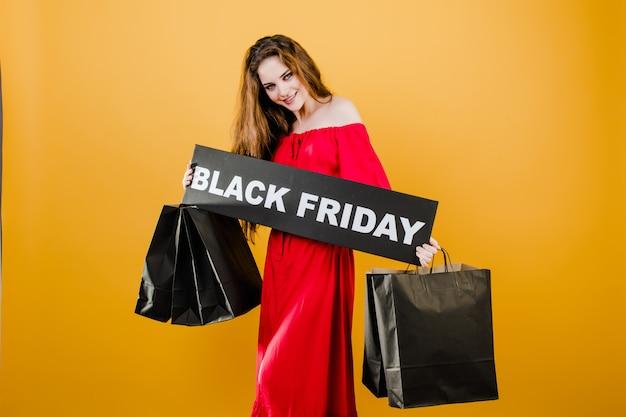 Giovane donna in vestito rosso con il segno di venerdì nero e sacchetti della spesa di carta isolati sopra giallo