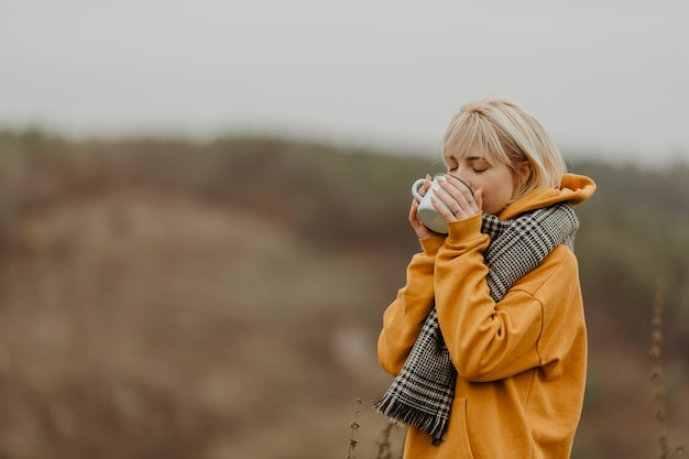 Giovane donna in viaggio d'inverno, bere il tè