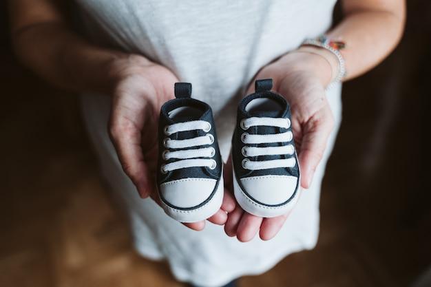 Giovane donna incinta a casa che tiene le scarpe per bambini